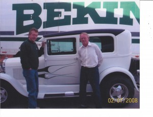 an old car and two men in front of a Bekins truck