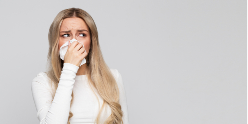 Woman with severe allergies holding a tissue up to her nose and looking upset