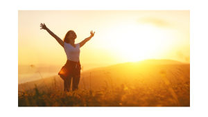 Happy woman jumping at sunrise
