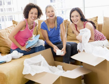 Three girl friends unpacking box's in new home smiling to camera
