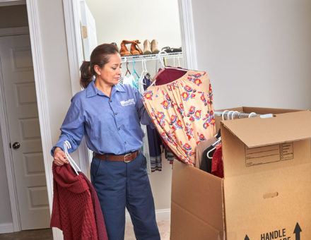 wheaton worker packing clothes into a box