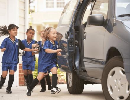 little kids in soccer jerseys running to get into van