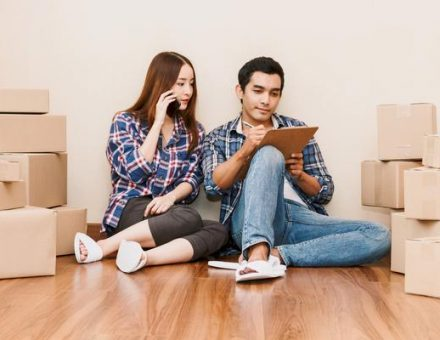 Couple sitting in a room full of boxes doing their moving prep: making a checklist and calling their moving company