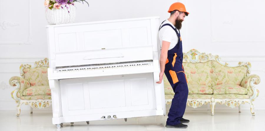 Mover in hard hat struggling to move a fragile piano by himself