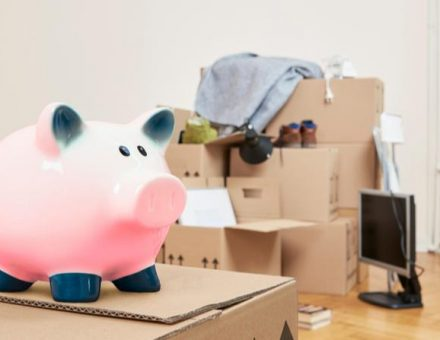 piggy bank on top of a moving box with more moving boxes in the background
