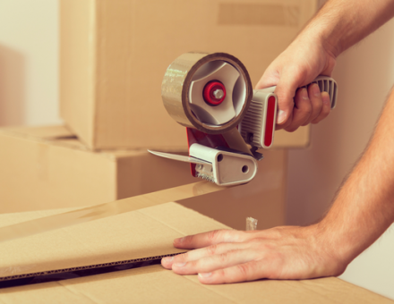 Taping up a cardboard box. What are the best ways to make packing for a move less stressful?
