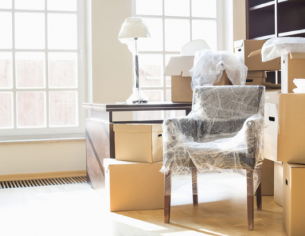 Wrapped up furniture surrounded by moving boxes