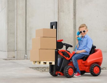 Kid in sunglasses driving a miniature forklift with moving boxes on it