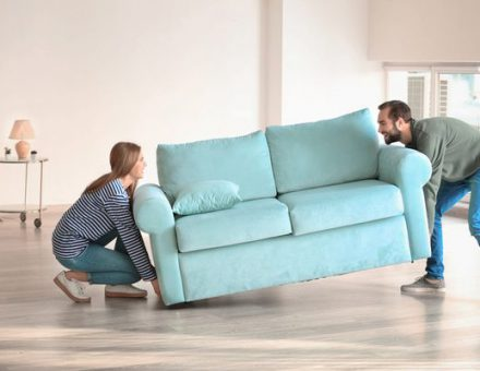 Couple struggling to carry a couch across the floor of their new home
