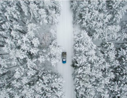 Car driving on a snowy single-lane road in the woods