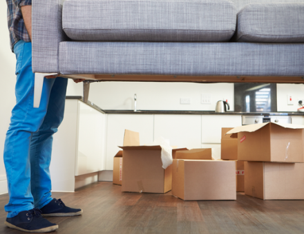 Person lifting couch with moving boxes in background