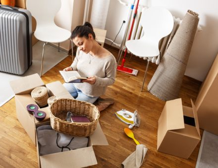 Young woman unpacking items from cardboard box