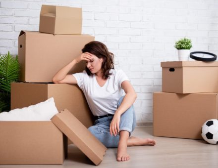 Stressed woman sitting with cardboard boxes on moving day