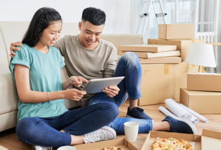 Man and woman sitting on the floor leaning on sofa with pizza and drinks after moving day
