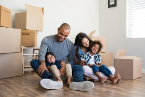 Family with young kids sitting by newly packed carboard boxes