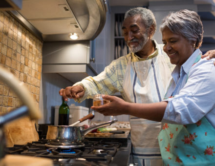 Smiling senior couple cook in the kitchen