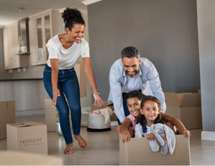 Smiling dad pushing excited daughters in cardboard box in new house while mom laughs