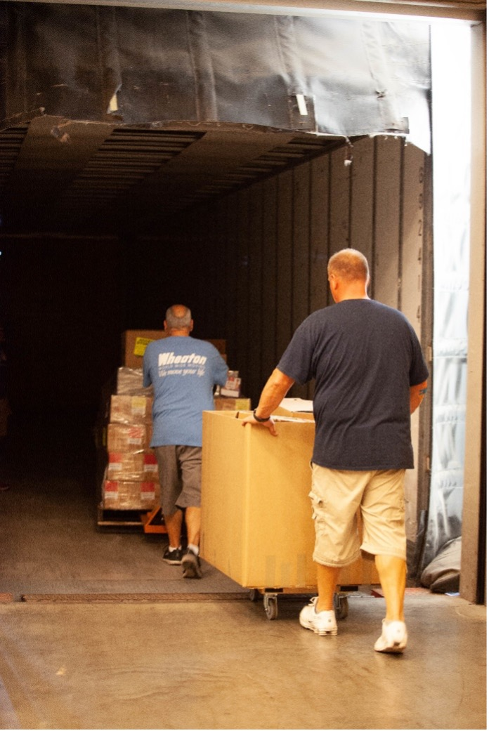 wheaton volunteers moving brown boxes