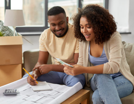 couple with blueprint and calculator counting money to create a moving budget
